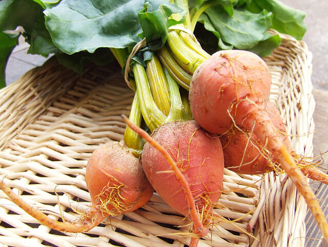 A bundle of small vegetables in a wicker basket.
