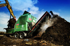 A digger turning an industrial compost heap.